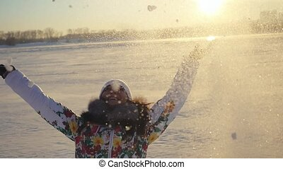 Happy pretty woman having fun and throwing the snow in winter field on sunset city background in slow motion with lense flare effects.