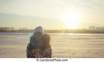 Happy cheerful woman having fun and throwing the snow in winter field on sunset city background in slow motion with lense flare effects.