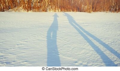Shadows of romantic couple hiking on snow in winter sunny day in slow motion. 1920x1080