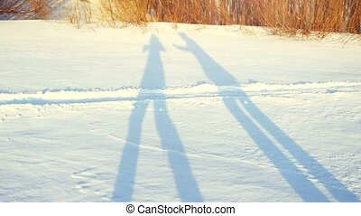 Shadows of romantic couple hiking on snow in winter sunny...