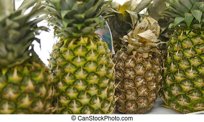 Moving past fresh pineapple in a supermarket grocery. Shelves with fruits at the shop. Close up