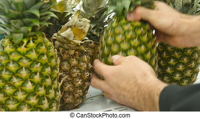 Male hand selecting pineapple at the supermarket. Man taking pineapple from counter in a grocery store. Guy selecting fresh fruit at produce department of shop. Buyer chooses food. Close up