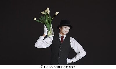 man mime with a bouquet of flowers on a black background.