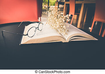 Old book open on table with reading glasses and classic...