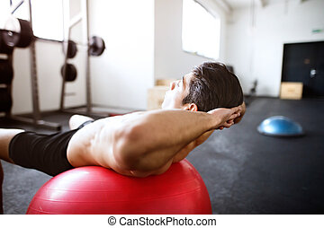 Fit hispanic man in gym training, working abs, doing...