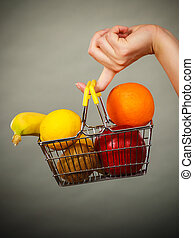 Woman holding shopping basket with fruits inside - Buying...
