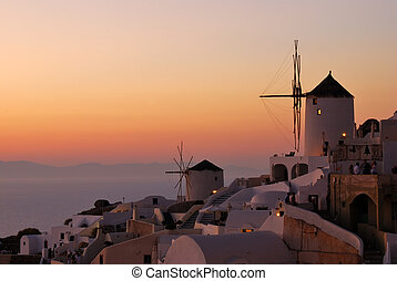 Oia sunset, in Santorini island (Greece). The tourists from...