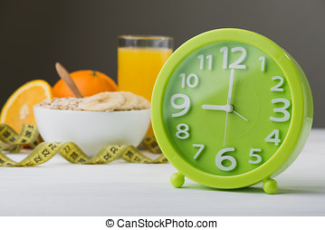 time health food - green clock against which the oatmeal and...