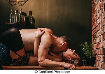 Passionate couple enjoying foreplay on kitchen table