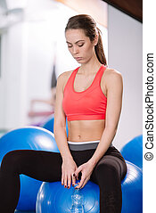 Young woman sitting on pilates balls and resting from...