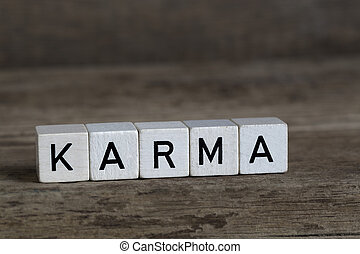 Karma, written in cubes on a wooden background