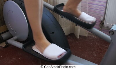 Young Woman Exercising on Elliptical Machine at Home