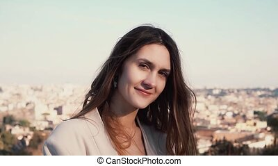 Portrait of young attractive woman standing on observation deck. Girl enjoying sunny day. Rome, Italy on a background.