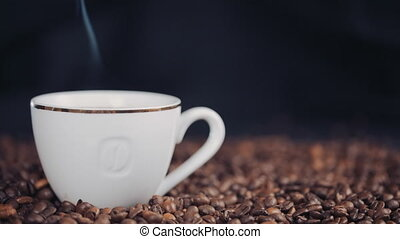 cup with hot drink on roasted coffee beans. Slow motion.