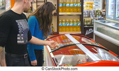 Young happy couple with shopping cart coming up to the the...