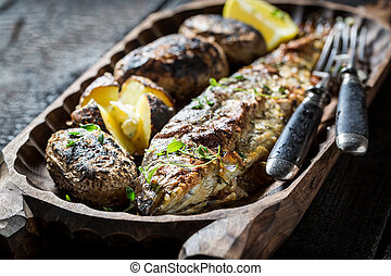 Homemade potatoes and trout fish with herbs and butter