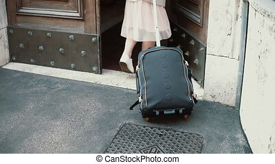 Young traveler woman walking with a suitcase in the street....