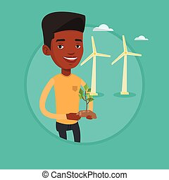Worker of wind farm holding green small plant.