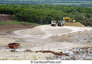 Truck working in landfill with birds looking for food. Garbage on the city dump. Soil pollution. Environmental protection.