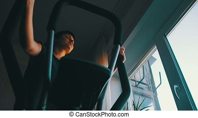 Silhouette of the Girl Exercising on the Cardio Trainer...