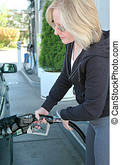 Gas pump - Female pumping gas into her car.