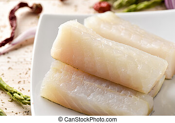 raw codfish - closeup of some slices of raw codfish in a...