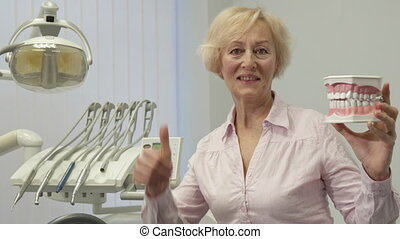 Woman holds layout of human teeth
