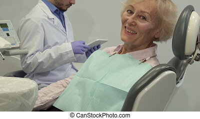 Female client shows her thumb up on the dental chair