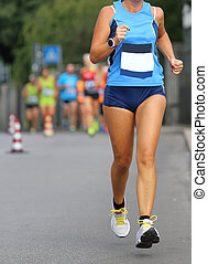 woman athlete running at the marathon in the city