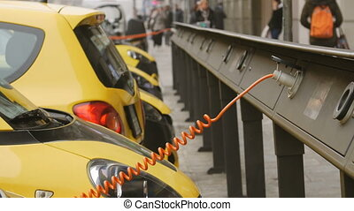 Electro car is charging in the street. - Small yellow...