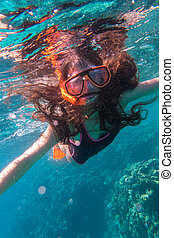Girl in swimming mask diving in sea near coral reef - Girl...