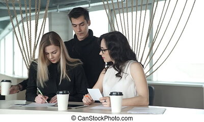 Two females office worker sitting at table, man comes to...