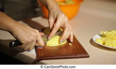 Woman is slicing potatoes on a wooden board.