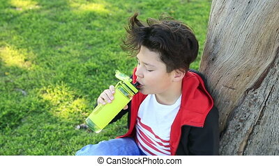 Child lying on green grass drinking water - Portrait of a...