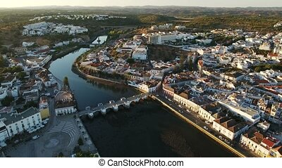 Aerial. Historical Tavira from the sky at sunset. The Roman...