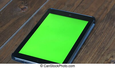 Men's Using Tablet PC with Green Screen on Wooden Table With...