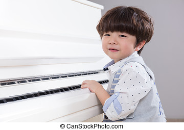 Happy Asian Chinese little boy playing piano at home - Happy...