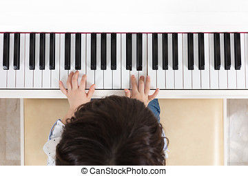 Aerial view of Asian Chinese little boy playing piano at...