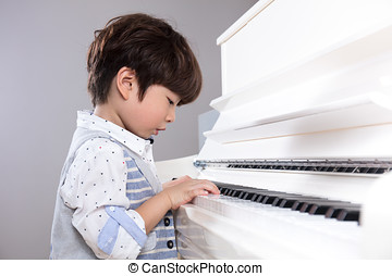 Asian Chinese little boy playing piano at home - Asian...