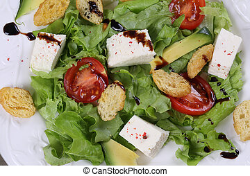 Salad with avocado , cheese, tomatoes and lettuce