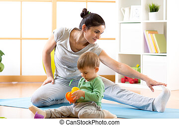 Sportive cute woman is engaged in fitness and yoga at home. Her son kid by near sitting and playing.