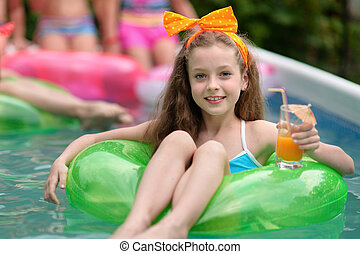 portrait of little girl in tropical style in a swimming pool