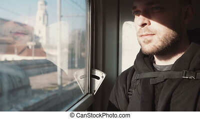 Handsome young man traveling by train. Attractive male...