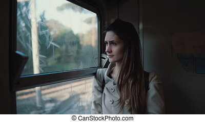 Young brunette traveling by train. Attractive girl looking...