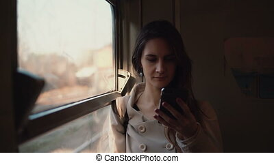 Young woman standing in the train and using smartphone. Attractive girl chatting with friends, browse the Internet.
