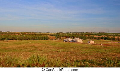 Motion Past Sunny Rural Landscape with Farmer Buildings -...