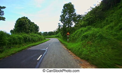 Motion down Country Curvy Road among Hilly Landscape under...