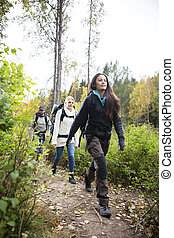 Female Hiker With Friends Walking On Forest Trail