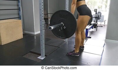 Young strong woman with perfect body in sportswear snatches heavy weight in gym. Female bodybuilder doing exercise - practicing deadlift at health club. Girl training - lifting barbell. Slow motion
