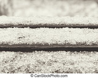 Late snow with hailstones on the old bench, black and white...